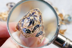 jeweler looking at jewelry through magnifying glass on vintage ring, jewerly inspect and verify, wedding ring in pawnshop