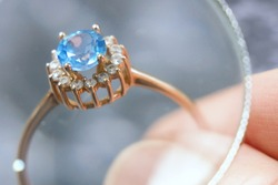 jeweler looking at ring with blue stone, jewerly inspect and verify, pawnshop concept, jewerly shop, closeup