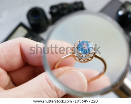 jeweler looking at ring with blue stone, jewerly inspect and verify, pawnshop concept, jewerly shop, closeup Foto stock ©