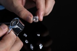 Jeweller checking diamond. Loose diamonds. Cut and polished diamonds. Hand with diamond. Diamond expert examining diamonds.