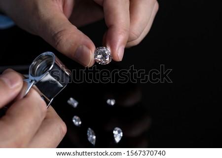Jeweller checking diamond. Loose diamonds. Cut and polished diamonds. Hand with diamond. Diamond expert examining diamonds.
