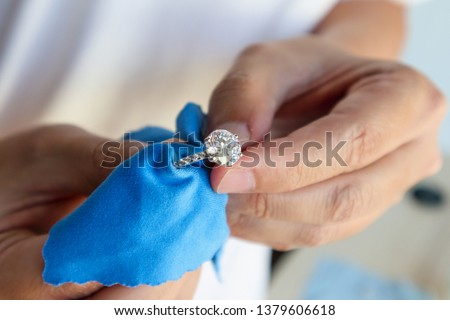 Jeweller hand polishing and cleaning jewelry diamond ring with micro fiber fabric stock photo
