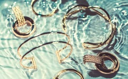 Jewellery branding, fashion gift and luxe shopping concept - Golden bracelets, earrings, rings, jewelery on emerald water background, luxury glamour and holiday beauty design for jewelry brand ads