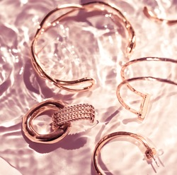 Jewellery branding, fashion gift and luxe shopping concept - Rose gold bracelets, earrings, rings, jewelery on pink water background, luxury glamour and holiday beauty design for jewelry brand ads