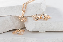 Jewellery set of hearts shape rose gold ring, pendant necklace and stud earrings on white background. Romantic  jewelry. Advertising still life product concept for Valentines Day