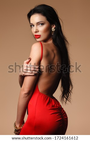 jewelry and beauty concept - beautiful brunette lady portrait in modern gems and red dress on nude background. Woman standing and demonstrating shoulder and back