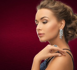 jewelry and beauty concept - beautiful woman in evening dress wearing diamond earrings and ring