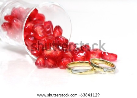 Jewelry and Food Series: pomegranate seeds and marriage rings, macro, high-key.