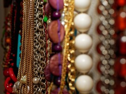 Jewelry at home used as interior decoration. Long colored necklaces made of gold, pearls, stones and silver hung on the wall of a bedroom.