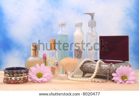 Jewelry Box With Cosmetics, Flowers and Perfume on Blue Textured Background