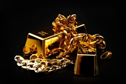 Jewelry buyer, pawn shop and buy and sell precious metals concept theme with a pile of golden rings, necklace bracelet and gold bullion isolated on black background