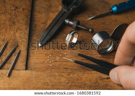 Jewelry craftsmanship. Jeweler holds tweezers. The jeweller engraver tools and golden ring, diamonds on wooden vintage desk. Tweezers, Magnifier, Chisel Hand Engraving, diamonds engagement ring