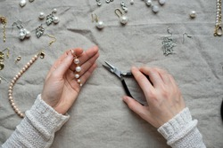 Jewelry designer working in studio with tools making pearl earrings. Close-up of female hands working with jewelry tools