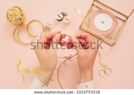 Jewelry designer workplace. Woman hands making handmade jewelry. Freelance fashion femininity workspace in flat lay style. Pastel pink and gold Stockfoto ©