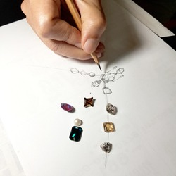 Jewelry designers are painting the necklace with a pencil on a piece of paper before the model can be produced.