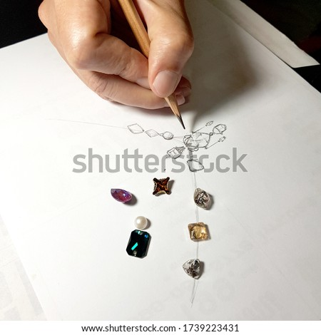 Jewelry designers are painting the necklace with a pencil on a piece of paper before the model can be produced. Foto stock ©