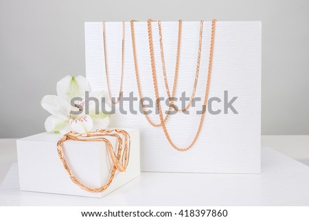 Jewelry gold set of chains and bracelets next to white lily on white background stock photo