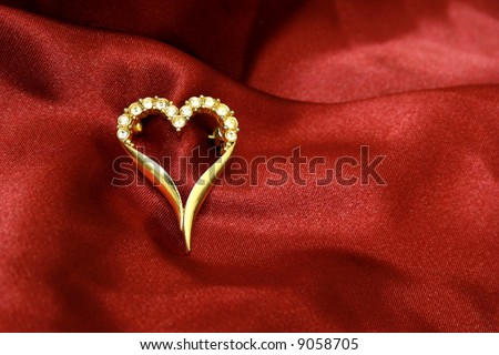 Jewelry golden heart on red silk