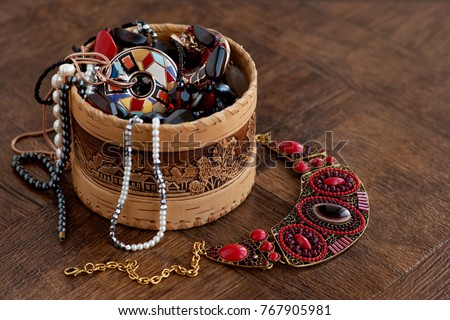 Jewelry in a wooden box. Many jewelry piled in a wooden box. Beads, pearls, pendants, pendants, chains on a brown wooden background. Design, fashion and style of jewelry.