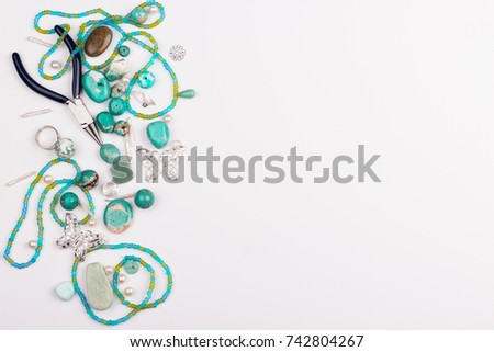 Jewelry making and beading process. Turquoise stones, glass beads, perl beads, silver findings and pliers on white background. Hobby, handmade,fine arts. Selective focus.