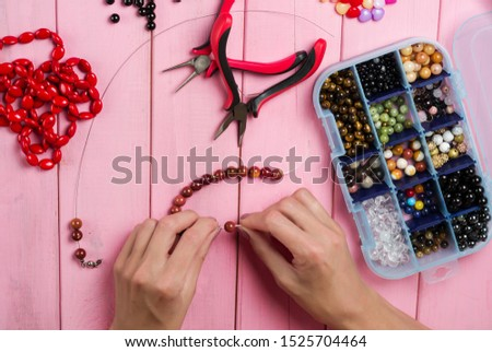Jewelry making. Making bracelet of colorful beads. Female hands with a tool on a pink wooden table.  #1525704464