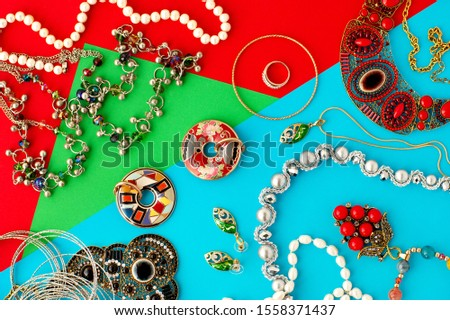 Jewelry on a colorful background. Jewelry and jewelry are accessories in women's fashion. Pearl beads, necklaces, pendants, pendants on a colored background. #1558371437