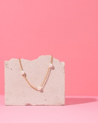 Jewelry on a pink background. Stylish  gold rings and necklace with different design on pink background. Product concept for jeweler