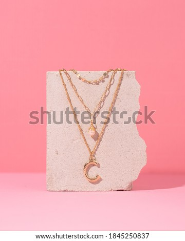Jewelry on a pink background. Stylish  gold rings and necklace with different design on pink background. Product concept for jeweler Foto d'archivio ©
