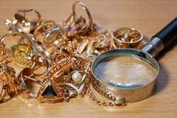 jewelry, pawn shop and buy and sell golden rings, necklace bracelet o wooden background, closeup