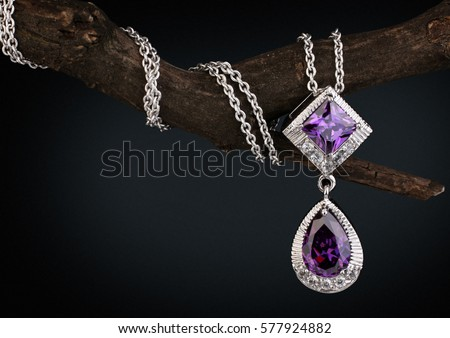 Jewelry  pendant witht gem  amethyst on twig, black background