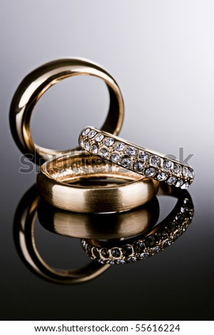 Jewelry photography. Three gold rings on gradient reflective surface.