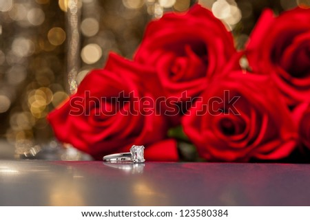 Jewelry ring and roses in front of a gold glitter background