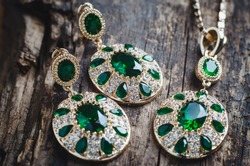 Jewelry set, earrings and pendant with green stones on a wooden background