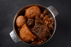 Jewish cuisine - Cholent (Hamin).Traditional main dish for Jewish Shabbat lunch, slow cooked beef Stew with potato, beans, barleys, wheat and brown eggs in a metal casserole
