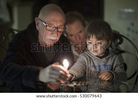 Jewish Family lighting Hanukkah Candles in a menorah for the holdiays ストックフォト ©