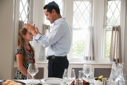 Jewish father blesses daughter by table set for Shabbat meal