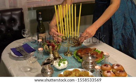 Jewish festival of lights. Latkes (potato pancakes) and sufganiyot jelly doughnuts foods cooked in oil—are customarily eaten during Hanukkah. Festive family dinner, menorah with candles Сток-фото ©