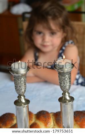 Jewish girl looks at lit sabbath candles before shabbat eve dinner.