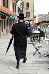 Jewish Hasidic Man with an umbrella walkind in the street in the Jewish Quarter