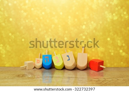Jewish holiday Hanukkah background with spinning top dreidel over gold bokeh. Copy space for text. The Hebrew letters are the first letters of the words \