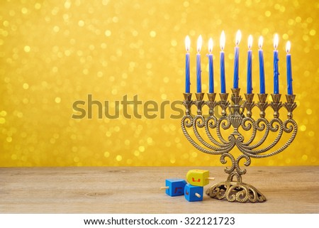 Jewish holiday Hanukkah background with vintage menorah and spinning top dreidel over lights bokeh. The Hebrew letters are the first letters of the words which means \