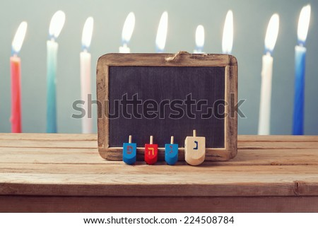 Jewish Holiday Hanukkah background with wooden dreidel spinning top and chalkboard over candles