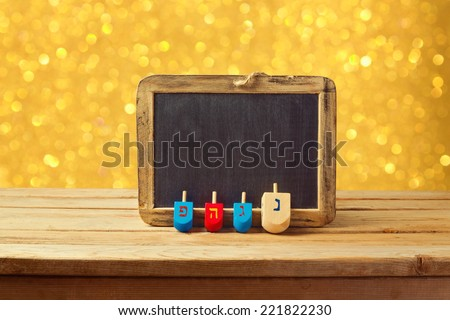Jewish Holiday Hanukkah background with wooden dreidel spinning top and chalkboard over golden bokeh lights