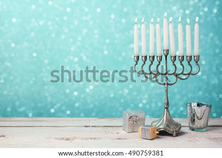 Jewish holiday Hanukkah celebration with menorah, dreidel and gifts on wooden table