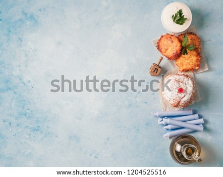 Jewish holiday Hanukkah concept and background. Hanukkah food doughnuts and potatoes pancakes latkes, oil and traditional spinnig dreidl on blue background. Top view or flat lay. Copy space for text.