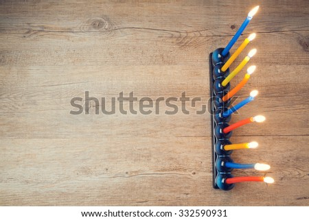 Jewish holiday Hanukkah creative background with menorah on wooden table. View from above.  Retro filter effect.