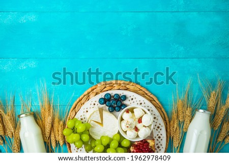 Jewish holiday Shavuot celebration concept with cheese, milk bottle, wheat ears and fruits on wooden blue table background