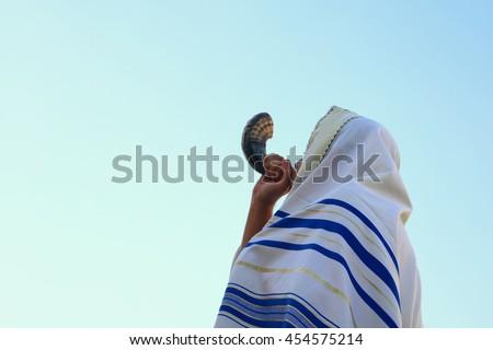 Jewish man blowing the Shofar (horn) of Rosh Hashanah (New Year). Religious symbol.