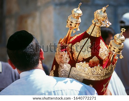 Jewish man in black kippah carrying a Torah scroll in a beautifully ornate red case with golden bells and crowns (rimmonim) and other decorations - Simchat Torah; Western/Wailing Wall, Jerusalem
