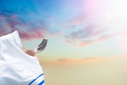 Jewish man in Tallit blowing the Shofar (horn) of Rosh Hashanah (New Year Jew) on sunset sky.Religious and Holidays symbol concept.